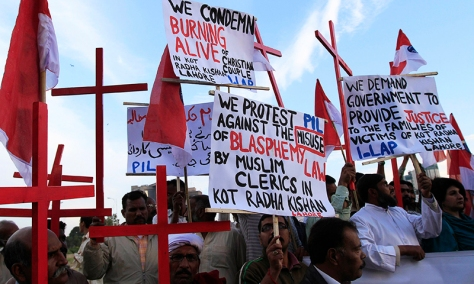 Members of the Pakistani Christian community hold placards and wooden crosses during a demonstration to condemn the death of a Christian couple in a village in Punjab province on Tuesday, in Islamabad