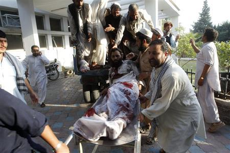 Afghan men carry a man injured in a bomb blast to a hospital in Jalalabad