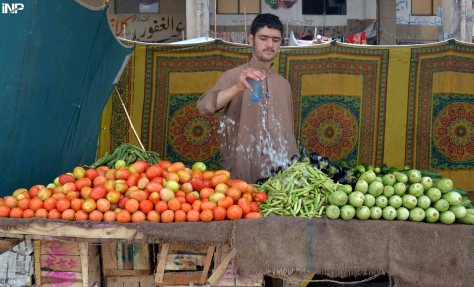 QUETTA: A vendor sprinkle water on vegetable to keep them fresh at his stall at Sasta Ramzan Bazar. INP PHOTO by Adnan Ahmed